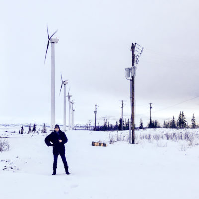 Man in heavy jacket stands in front of large array of wind turbines