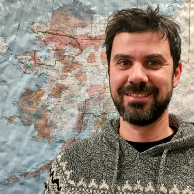 Bearded man stands in front of large map of Alaska