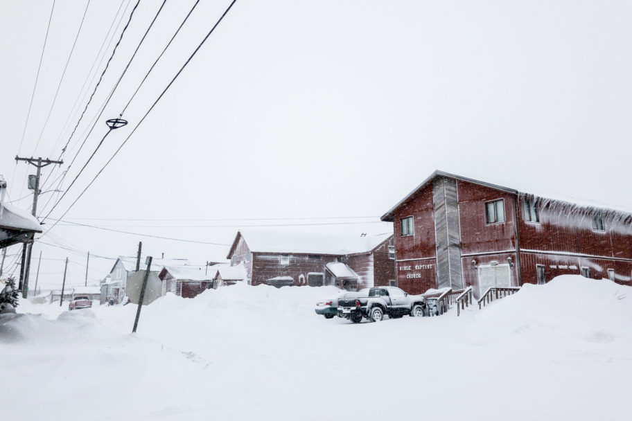 A streetcorner in Nome dominated by recent snowfall, with drifts on both sides of the street.