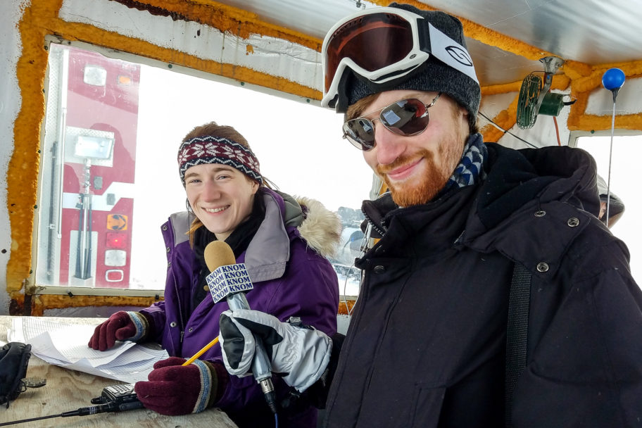 Karen and Gabe, wearing heavy parkas, smile inside a small shack near the start line of the Nome-Golovin Snowmachine Race.