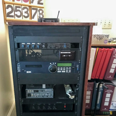 In the corner of a Catholic church, a rack of broadcasting hardware, such as a transmitter and CD player.