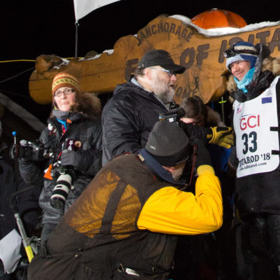 At Iditarod finish line, musher interacts with race officials and smiles for press photos.