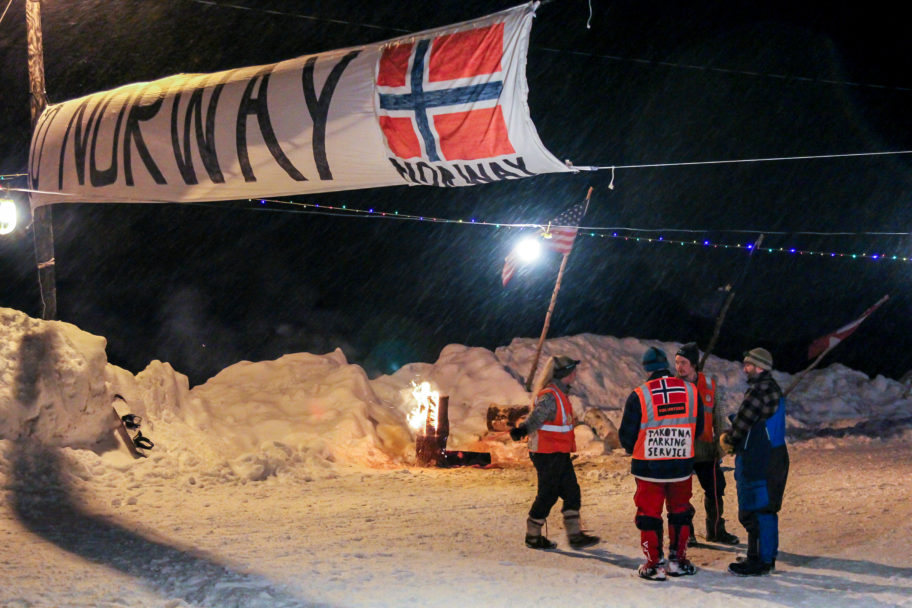 "Group of Iditarod handlers standing under a large banner with the word ""Norway"" and a Norwegian flag."