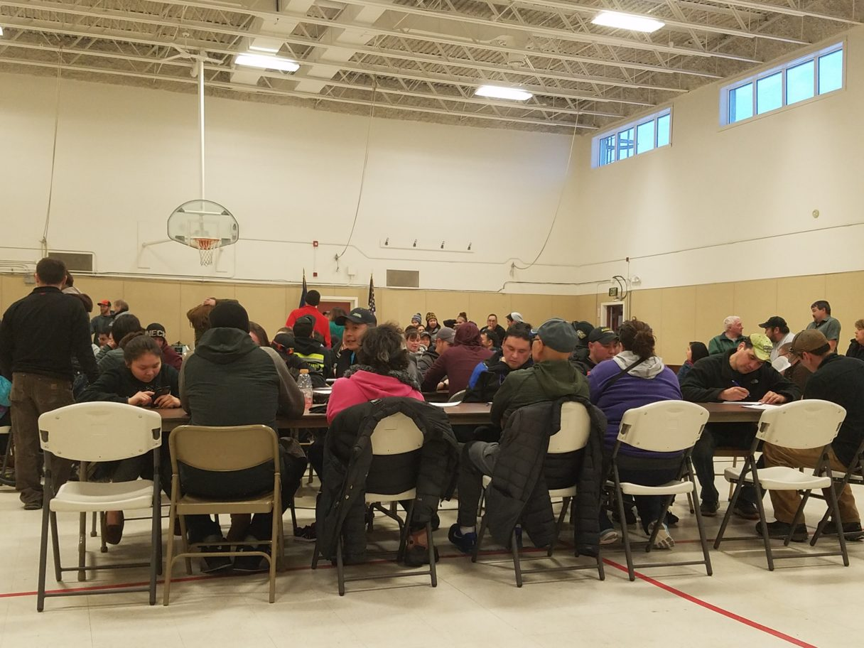 Racers sit at long tables set up in the Armory for the official sign-up of the 2018 Nome-Golovin Snowmachine Race.