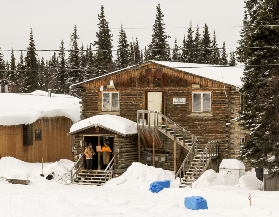 Large, log-cabin-style building surrounded by snowy forest