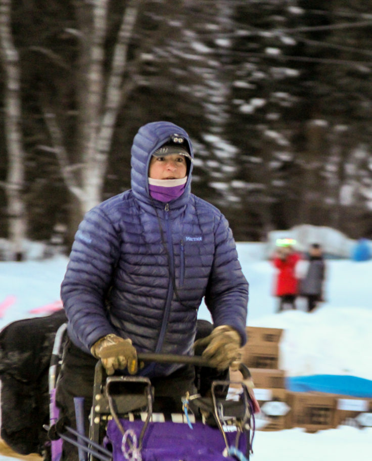 Musher in purple parka leaving an Iditarod checkpoint