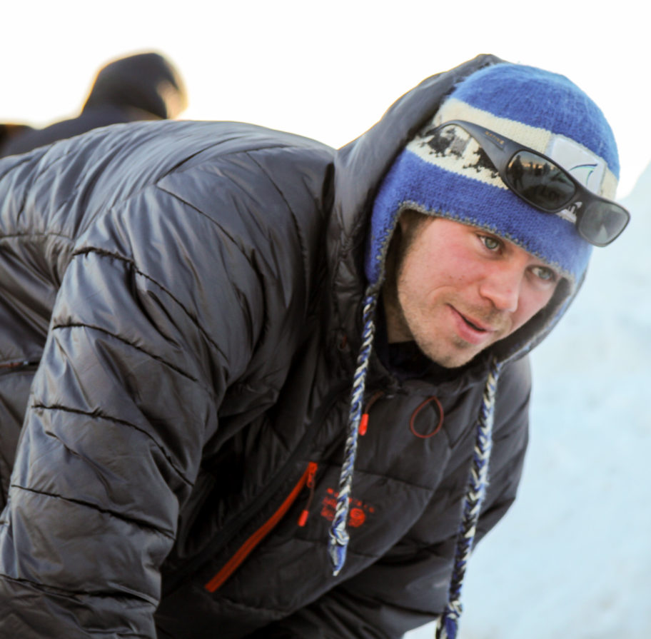 Joar Ulsom, wearing a blue hat and black parka, attends to his sled dogs in Unalakleet on Sunday.