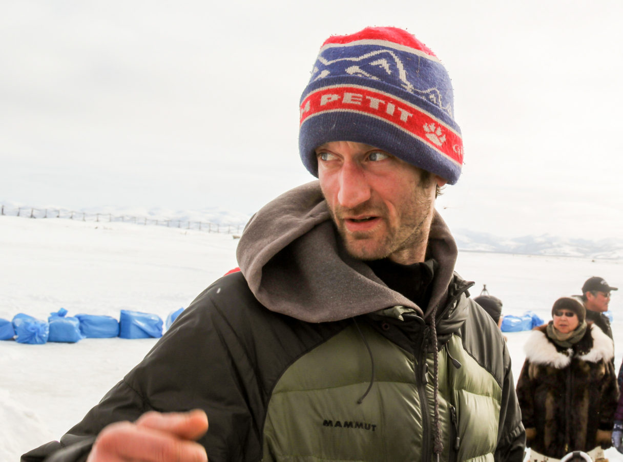 "Iditarod musher Nic Petit, wearing ""Petit"" hat, looks around at the Unalakleet checkpoint"