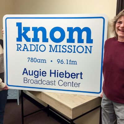 "Two women stand next to a large sign reading ""KNOM Radio Mission 