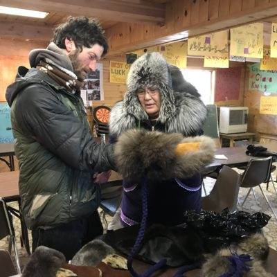 Kobuk 440 champion Nicolas Petit tries on a pair of fur mittens sewn by Myra Yupikson.