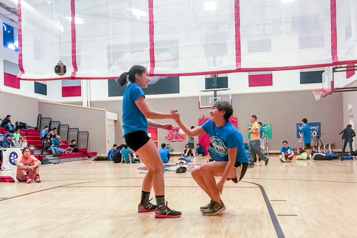 One NYO athlete helps another stand up from the gymnasium floor.