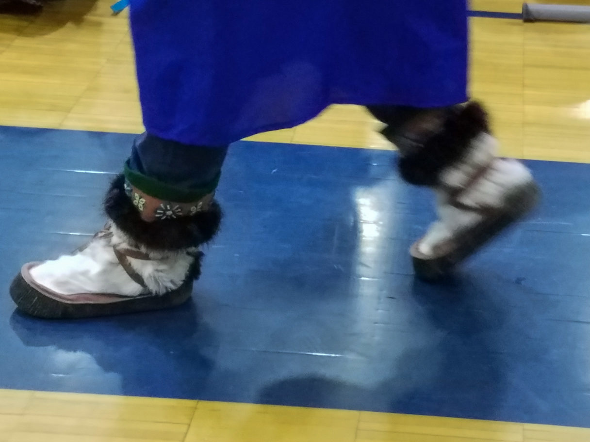 A Class of 2018 NBHS Graduate wears mukluks with his robes.