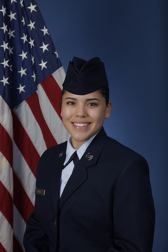 Woman in uniform poses in professional portrait, smiling in front of American flag.