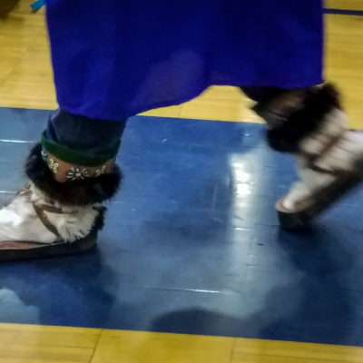 A high school graduate walks on a gymnasium floor in her graduation gown, wearing traditional, Alaska Native mukluks.
