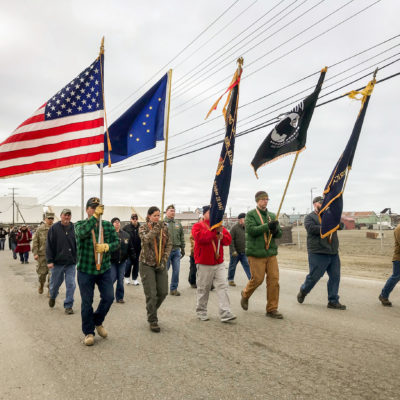 Color guard, bearing flags, leads the 2018 Memorial Day parade through Nome.