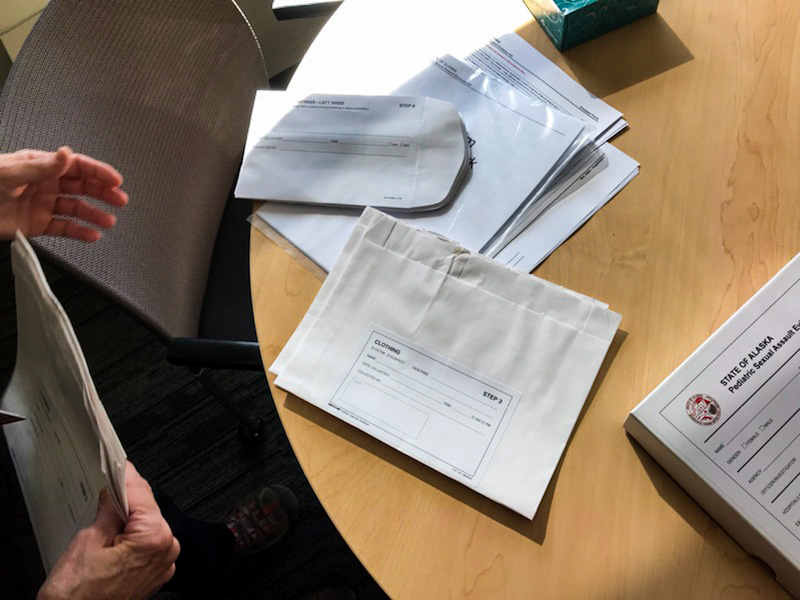 The evidence collection envelopes that compose a sexual assault examination kit are spread across a table.