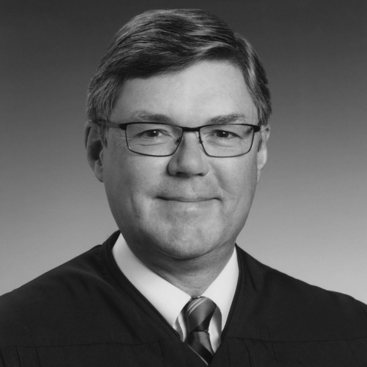 Black-and-white photo of man in glasses wearing shirt and tie and judicial robe.