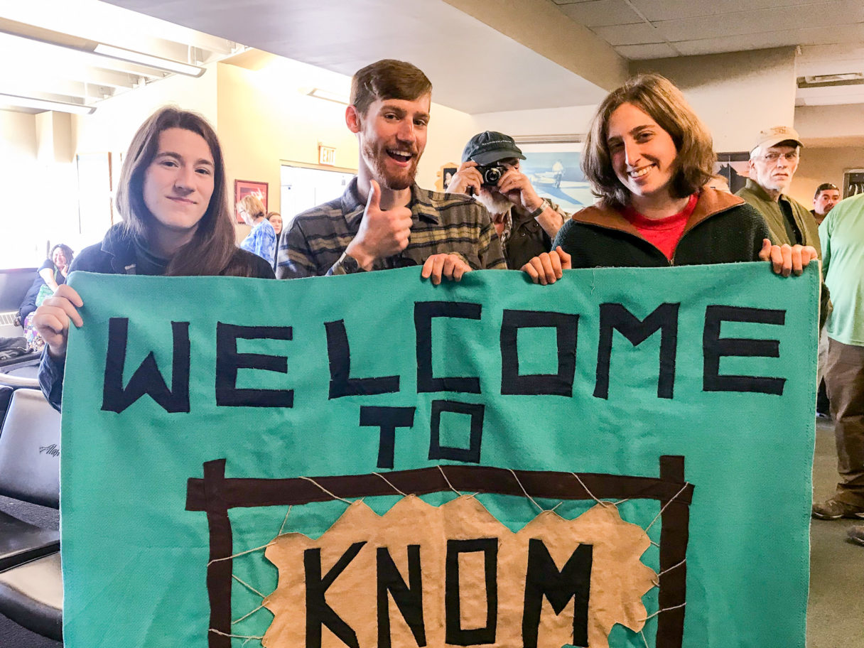 """Three people hold a teal """"Welcome to KNOM"""" banner inside a small airport terminal, while a man, standing over their shoulder, holds his own small camera back at the photographer."""