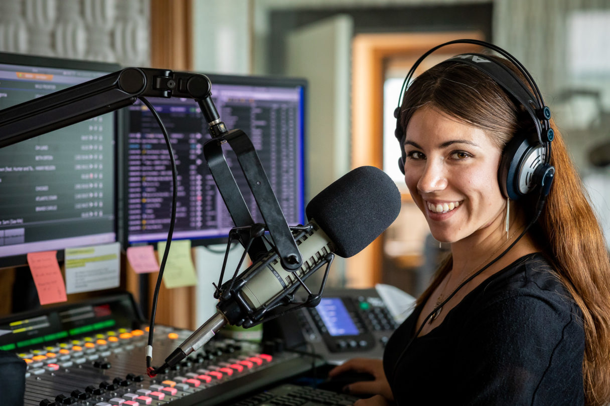 Woman inside KNOM radio studios stands behind microphone and sound board, smiling at the camera.