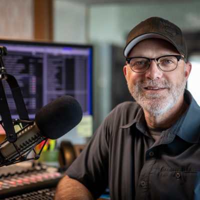 Man smiles, standing in front of radio microphone and sound board.