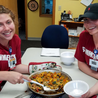 "Two women in dark red ""Summercise"" t-shirts smile at camera, sitting at a table inside KNOM studios, while displaying skillet with freshly-cooked egg scramble."