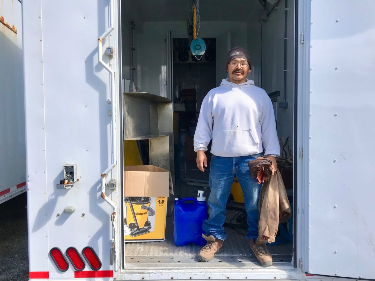 Man in a white hoodie and jeans stands inside the door of a trailer