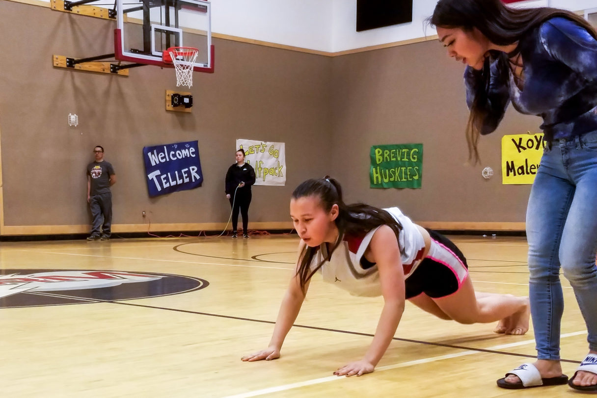 """Girl is in position on gymnasium floor similar to a push-up — body almost parallel to the floor, legs behind her, arms extended — while competing in the Native Youth Olympics """"seal hop"""" event."""