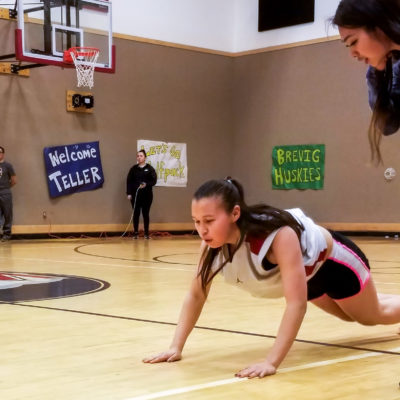 "Girl is in position on gymnasium floor similar to a push-up — body almost parallel to the floor, legs behind her, arms extended — while competing in the Native Youth Olympics ""seal hop"" event."