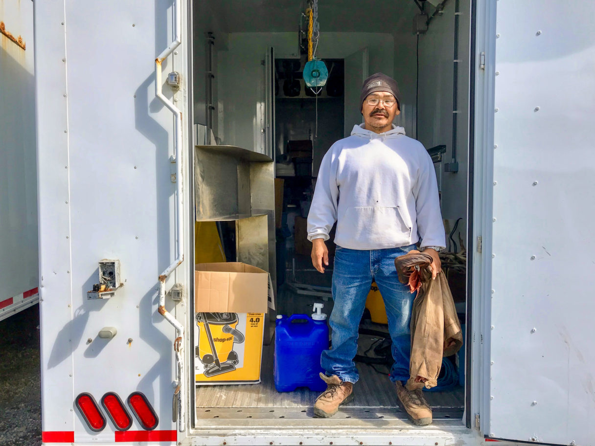 Man stands at the doorway to a mobile reindeer processing plant.