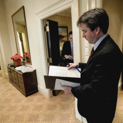 Man in dark suit stands inside the White House, looking at a folder of papers.