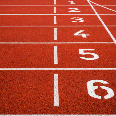 A reddish brown cross-country track, with a close-up view of the starting lines.