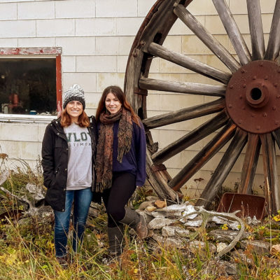 Two women, wearing autumnal jackets, stand next to a cabin situated among high grass along a rural Alaska coastline.