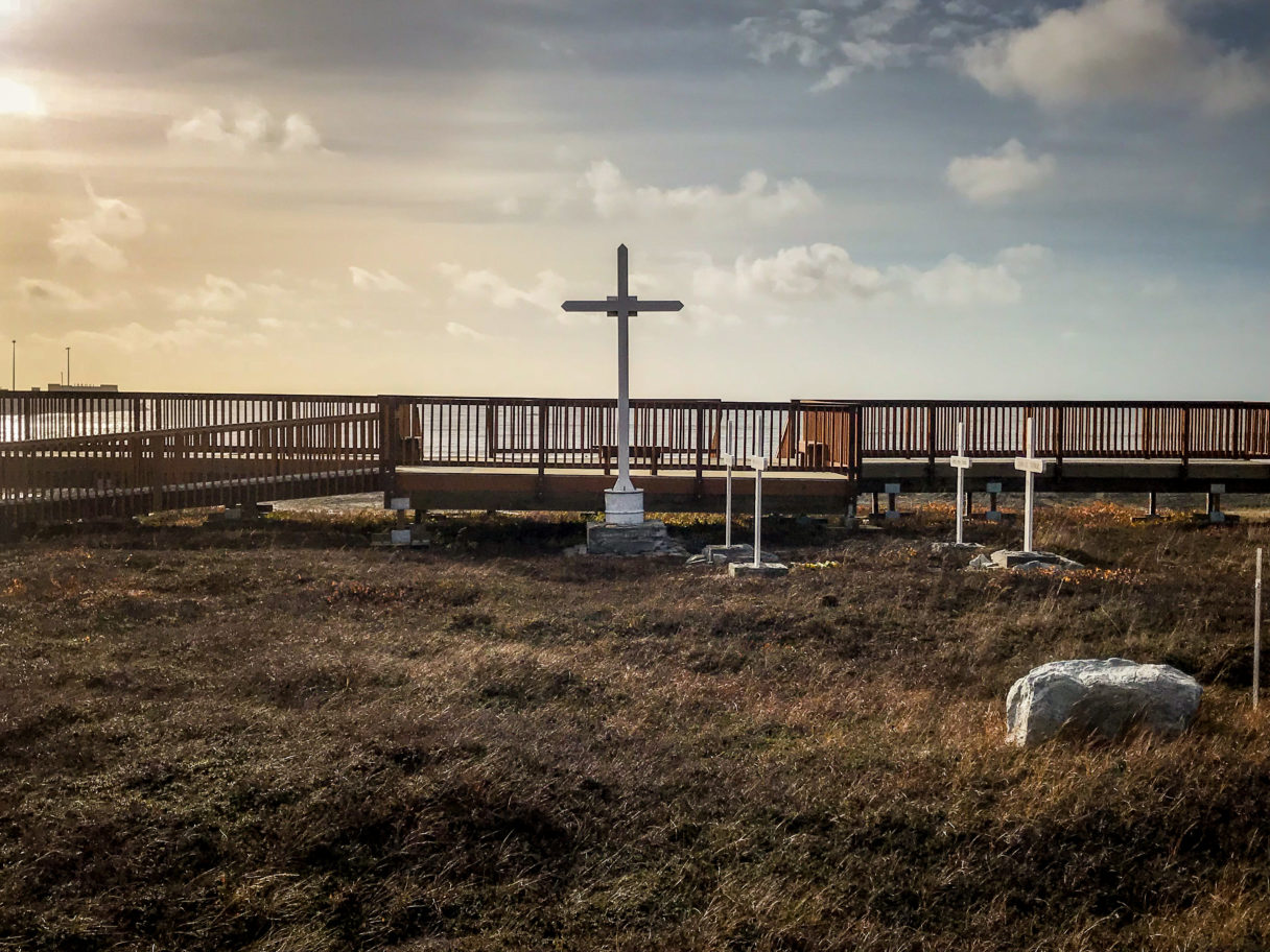 Landscape of cemetery with afternoon sky and Bering Sea in background.