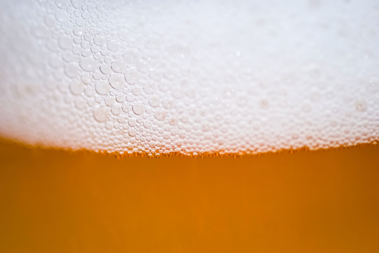 Very close, macro view of beer poured into a glass.