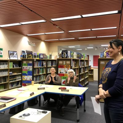 a woman stands smiling looking to the left, as two seated women look on and applaud in a school library.
