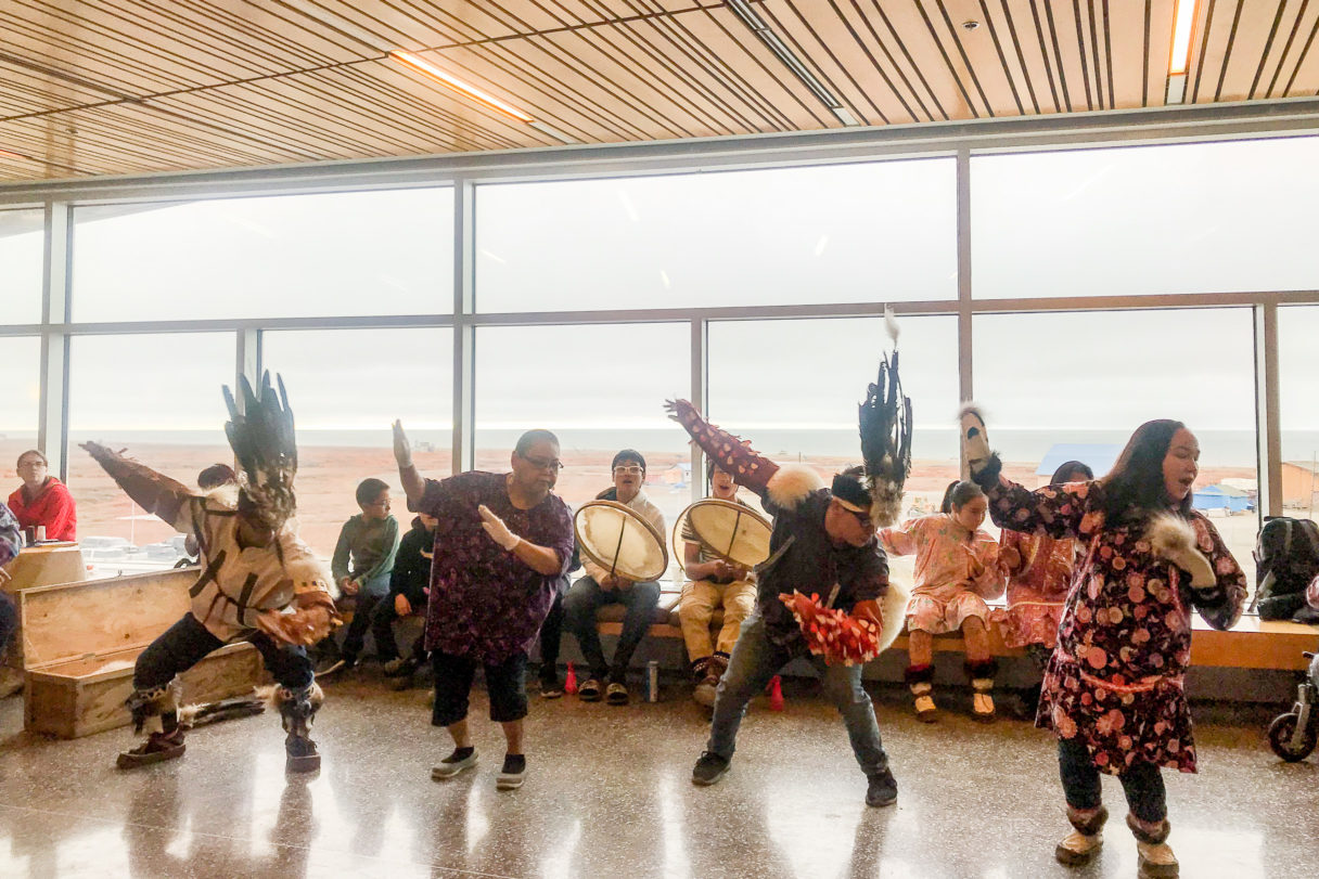 Alaska Native dance ensemble, mid-performance, next to a window overlooking Nome, Alaska.