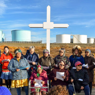 Choir sings in front of large white cross, outside, with large fuel tanks in the background on a sunny autumn day near Nome.