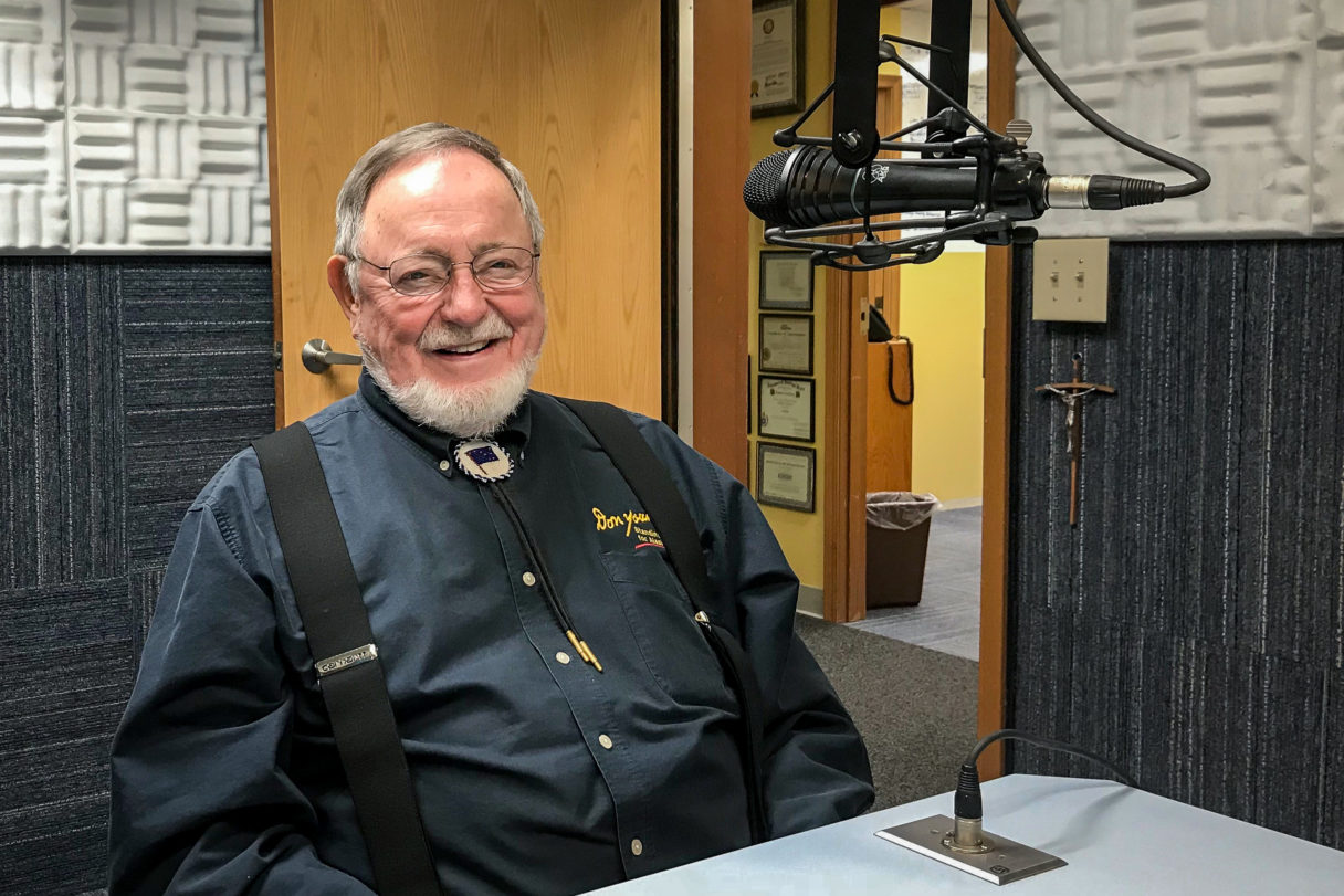 Bearded man in blue shirt and bolo tie sits, smiling at camera, in front of radio microphone.