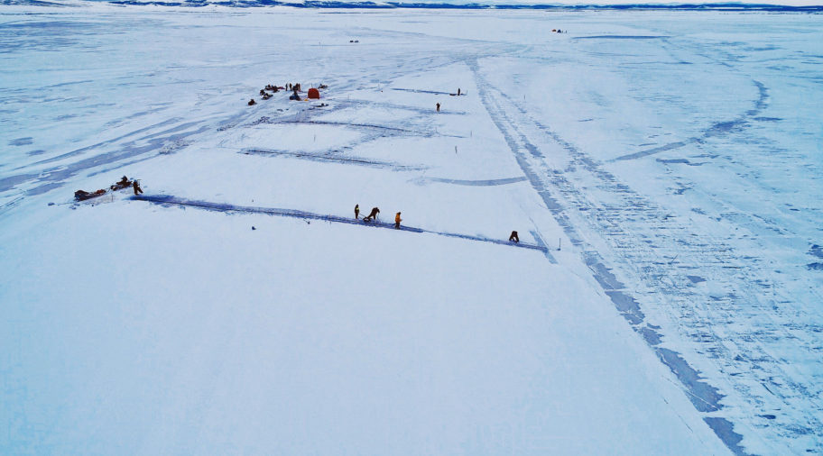 Aerial view of search-and-rescue efforts on frozen sea ice near a remote Alaska village.