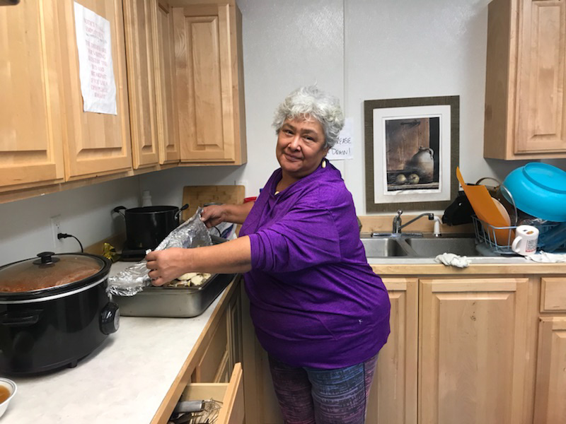 Woman standing next to kitchen stove.
