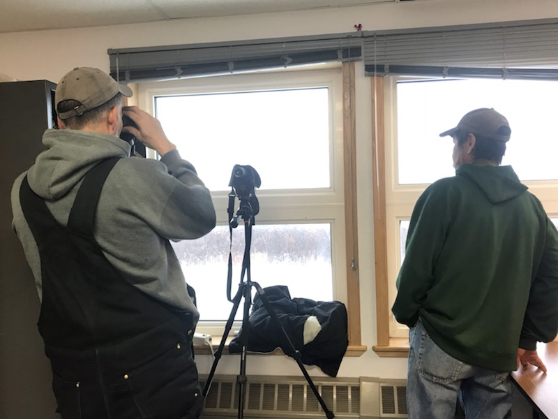 Two men, one with binoculars, look to the horizon through a pair of windows, scanning for returning searchers.