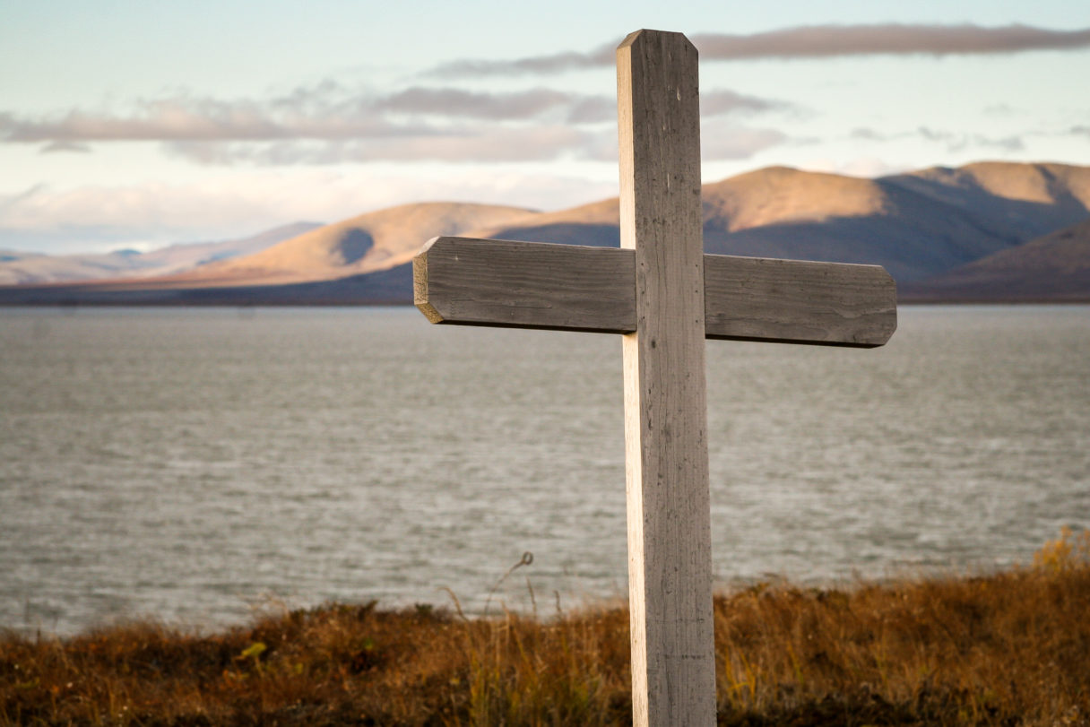 Wooden cross in foreground, large body of water and sub-Arctic mountain range in background