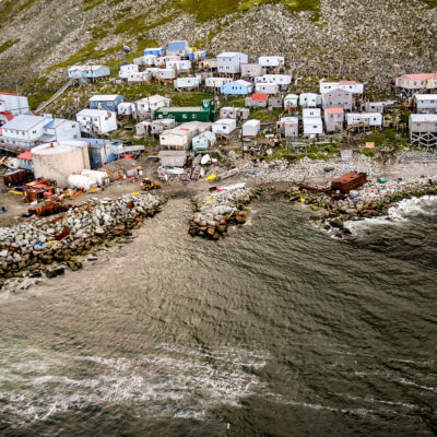 An aerial view of a small, coastal, island village nestled on the side of a hill.