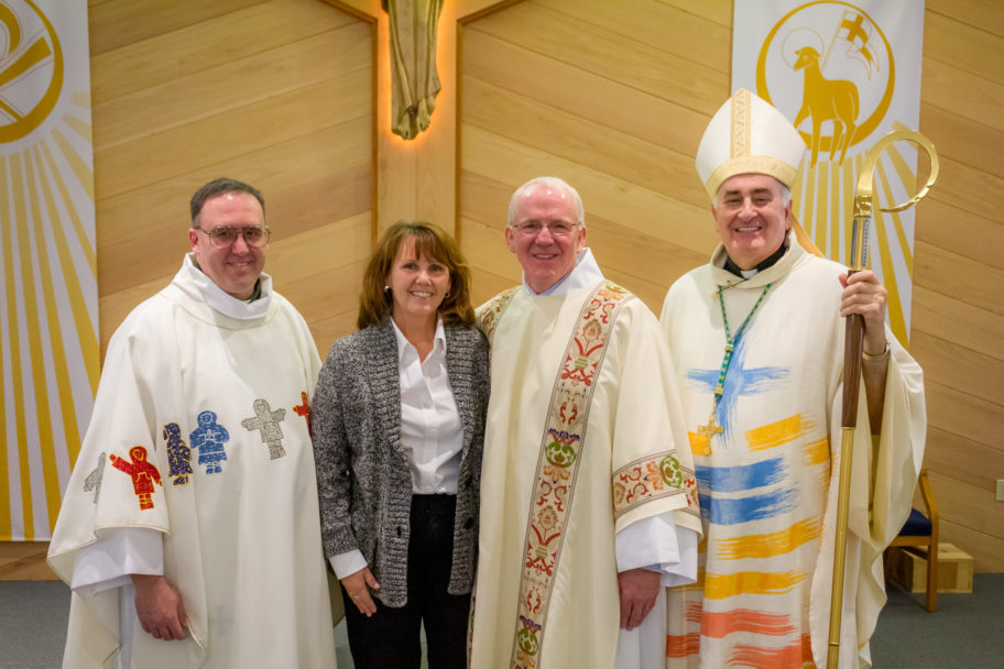 A priest, a bishop, a deacon, and a laywoman smile at the camera inside a Catholic church.