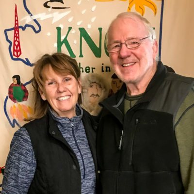 Married couple smile at camera inside of KNOM's radio broadcasting studio.