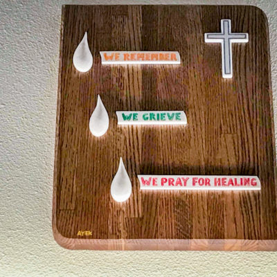 "A wooden plaque bearing a simple, white cross, three teardrop shapes, and the words ""We Remember, We Grieve, We Pray for Healing."""