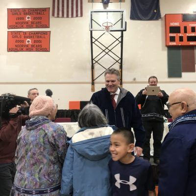 smiling man greets people in a gymnasium