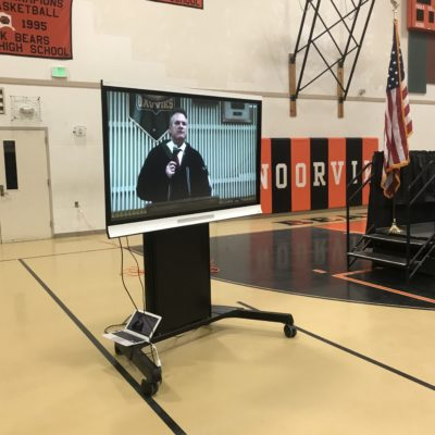 A large screen in a gymnasium depicts a man speaking on a microphone