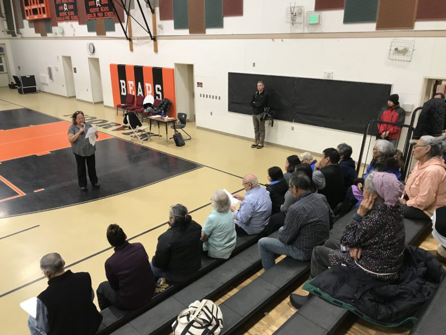 woman speaks in front of group of people sitting on bleachers in gymnasium