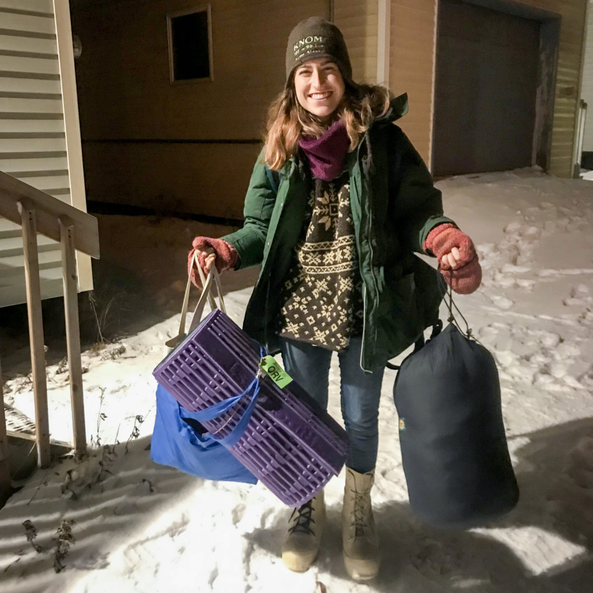 Woman stands smiling on snowy ground at night, holding camping gear and wearing heavy winter clothes.